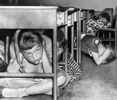 niños debajo de los escritorios